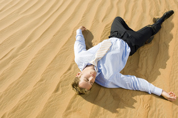 A man laying in a desert