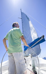 Man in green polo shirt standing at helm of sailing boat, steering, rear view, low angle view (lens flare)