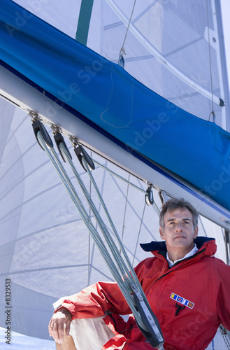 Man in red jacket sitting on deck of sailing boat below sail, smiling, low angle view