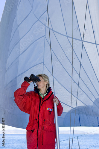 Woman in red jacket standing on deck of sailing boat below sail, looking through binoculars, leaning on mast