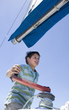 Boy (8-10) winding rope pulley of boat rigging on deck of sailing boat out at sea, smiling, low angle view