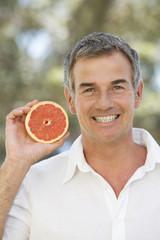 A man holding a grapefruit