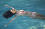 A young woman floating in a swimming pool