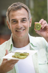 A man eating kiwi fruit