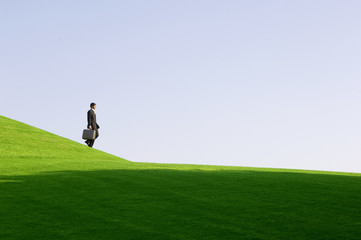 A businessman with a suitcase walking down hill