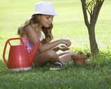 A young girl planting seeds in a plant pot