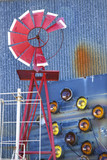 Windmill against blue corrugated metal building. poster