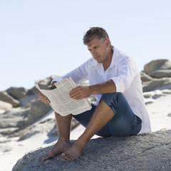 A man sitting on rocks reading a newspaper