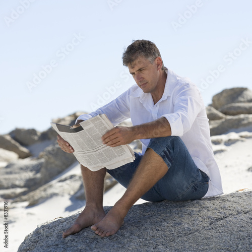A man sitting on rocks reading a newspaper