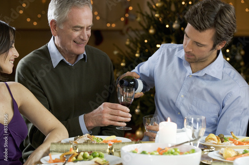 A son pouring his father a glass of wine