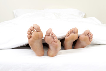 Close-up of feet of couple in bed