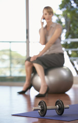 A businesswoman sitting in a gym using a mobile phone