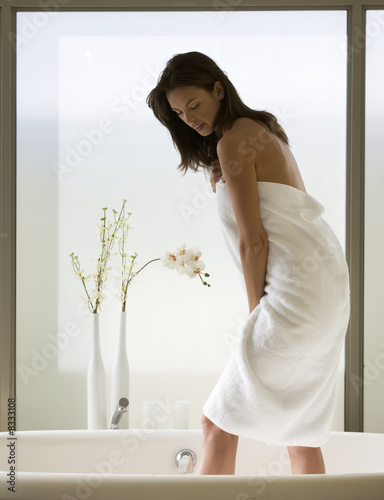 A young woman standing in a bath
