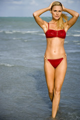A young woman in a bikini standing on a beach