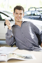 A young man with keys to a new car