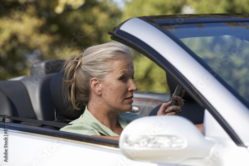 A senior woman driving a car whilst on a cell phone