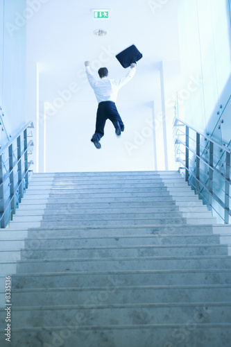 A businessman jumping at the top of stairs