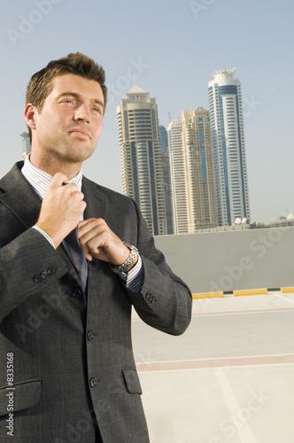 A businessman adjusting his tie