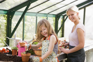Young girl and woman in greenhouse putting soil in pots smiling