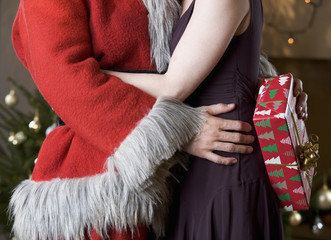 A couple at Christmas with the man wearing a Santa Claus Costume