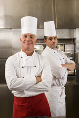 Two male chefs standing in commercial kitchen, arms folded, smiling, portrait