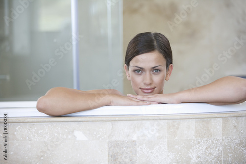 A young woman sitting in a bath