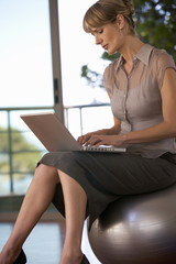 A businesswoman sitting in a gym using a laptop