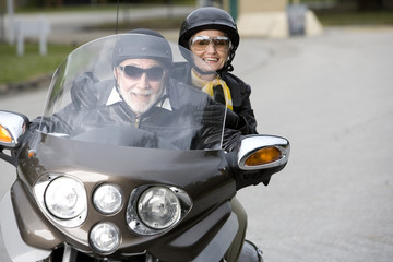 A senior couple on a motorbike