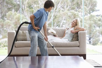 A young boy vacuuming whilst his mother relaxes