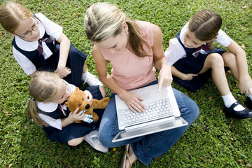 A teacher and children using a laptop outside