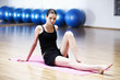 A young woman sitting on a yoga mat