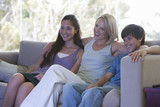 A mother watching TV with her children