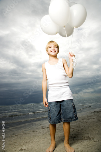 A young boy with a bunch of balloons