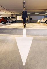 A businesswoman walking in a car park