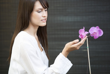A woman admiring an orchid flower