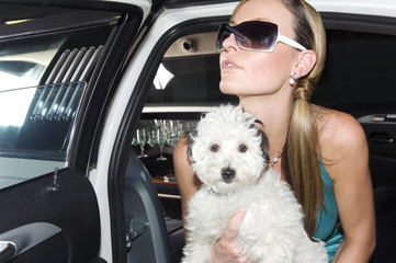 A woman in a stretch limousine with her pet dog