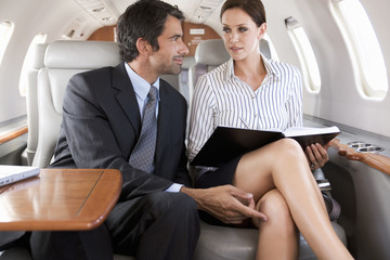 A businessman flirting with his PA on a flight