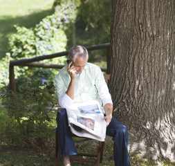 Man with a newspaper and mobile phone sitting next to a tree