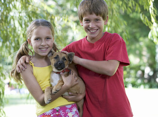 Young boy and girl holding a puppy