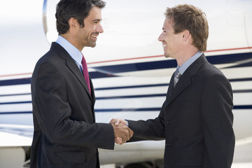 Two business colleagues shaking hands before departure