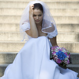A bride sitting on steps looking sad
