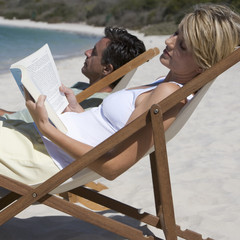 A mature couple relaxing in deckchairs on a beach