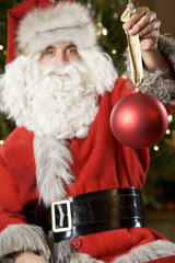 Father Christmas or Santa Claus holding a bauble