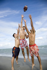 Three young men playing with a ball on a beach