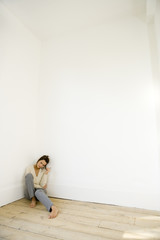 A young woman sitting in the corner of an empty room