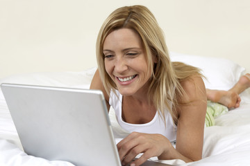 Young woman in bed working on laptop