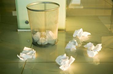 Waste paper scattered around a bin