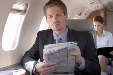 A businessman reading the paper on a plane