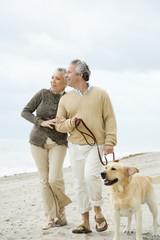 A senior couple walking their dog
