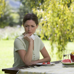 A woman looking sad and pensive sitting in the garden